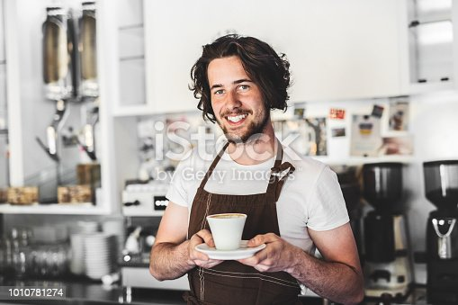 1003493404istockphoto Portrait of a professional barista holding a cup of coffee in a cafe. 1010781274