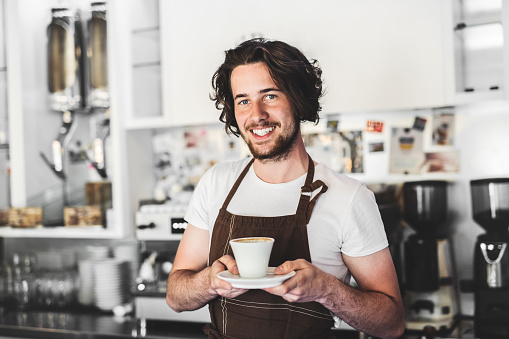 1003493404 istock photo Portrait of a professional barista holding a cup of coffee in a cafe. 1010781274
