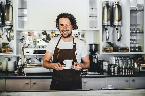1003493404 istock photo Portrait of a professional barista holding a cup of coffee in a cafe. 1031916098