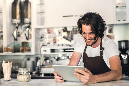 1003493404 istock photo Portrait of a professional barista holding a digital tablet in a cafe, reading. 1019457786