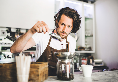 1003493404 istock photo Portrait of a professional barista working in a cafe. 980075738