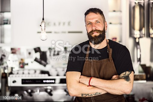 istock Portrait of a professional bearded barista behind a counter in a cafe, arms crossed. Copy space. 1003493404