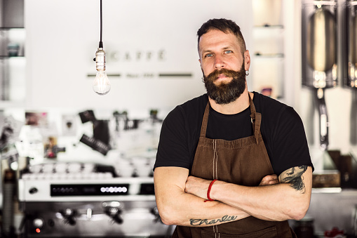 1003493404 istock photo Portrait of a professional bearded barista behind a counter in a cafe, arms crossed. Copy space. 1003493404