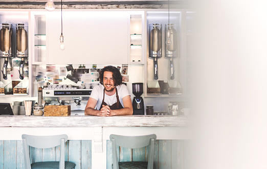 1003493404 istock photo Portrait of a professional bearded barista behind a counter in a cafe. 970860528
