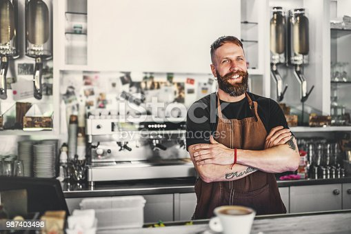 Mature handsome man standing in a coffee shop. A cup of coffee on a counter and a coffee machine in the backgrounds.
