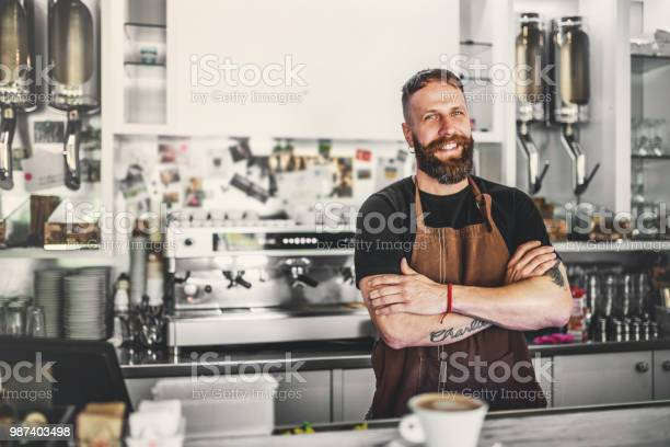 Portrait of a professional bearded barista behind a counter in a cafe picture id987403498?b=1&k=6&m=987403498&s=612x612&h=ghh59aiot2a1l40gkucboebhpad ub4slkh mrk7opc=