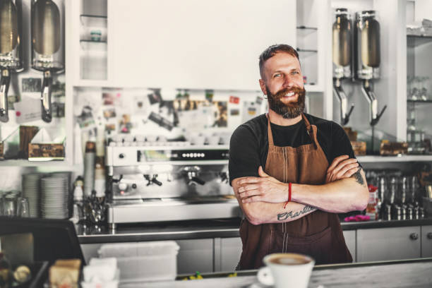 portrait of a professional bearded barista behind a counter in a cafe, arms crossed. - barista stock photos and pictures