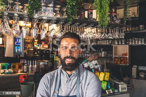 1003493404istockphoto Portrait of a professional bearded barista in front of a bar counter in a cafe with arms crossed 1180976386