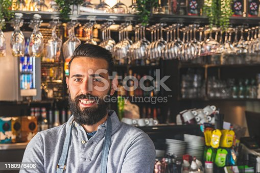 1003493404istockphoto Portrait of a professional bearded barista in front of a bar counter in a cafe with arms crossed 1180976406