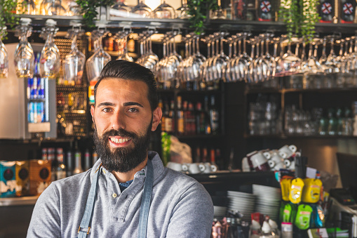1003493404 istock photo Portrait of a professional bearded barista in front of a bar counter in a cafe with arms crossed 1180976406
