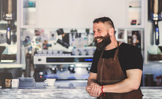 1003493404 istock photo Portrait of a professional bearded barista leaning on a counter in a cafe. 970860308