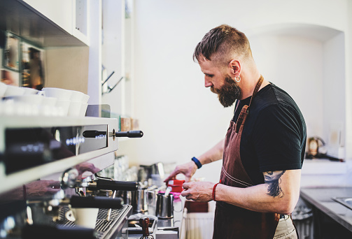1003493404 istock photo Portrait of a professional bearded barista making coffee in a cafe. 970860548