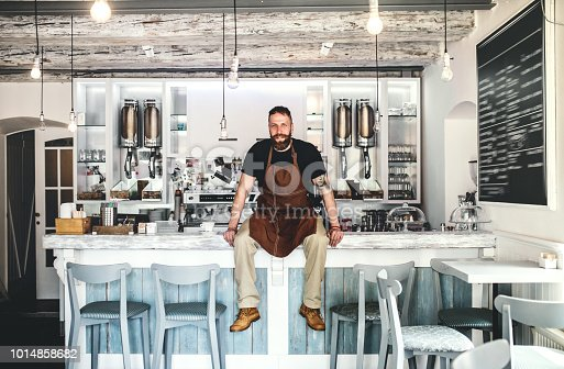 1003493404istockphoto Portrait of a professional bearded barista sitting on a counter in a cafe. 1014858682
