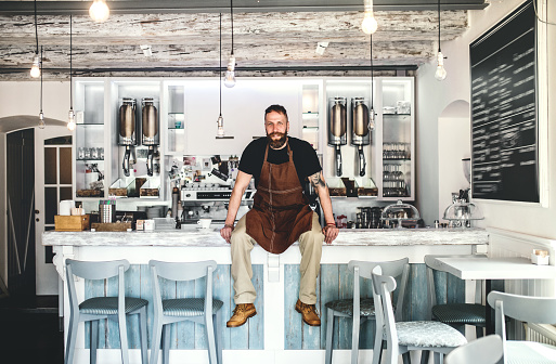 1003493404 istock photo Portrait of a professional bearded barista sitting on a counter in a cafe. 1014858682