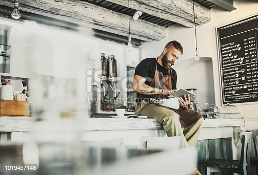 1003493404istockphoto Portrait of a professional bearded barista sitting on a counter in a cafe, using tablet. 1019457148
