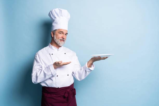 Porträt eines professionellen Kochs, der einen leeren Teller isoliert auf hellblau hält. – Foto
