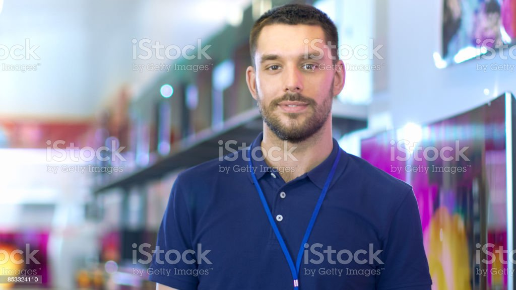 Portrait of a Professional Expert Consultant Smiles and Looks into Camera as Stands in the Bright, Modern Electronics Store Full of Latest Models of TV Sets, Cameras, Tablets and other Devices.The Depth of Field Shot. stock photo