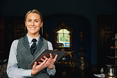 A shot of a beautiful blonde hotel receptionist standing inside a hotel, holding a digital tablet and looking positive.