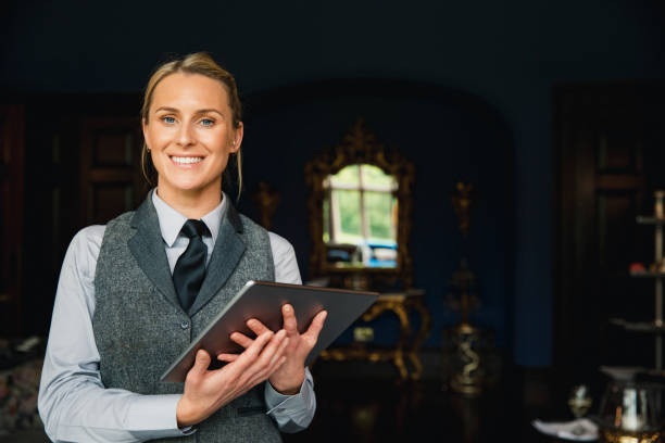 Portrait of a Professional Hotel Employee A shot of a beautiful blonde hotel receptionist standing inside a hotel, holding a digital tablet and looking positive. concierge stock pictures, royalty-free photos & images