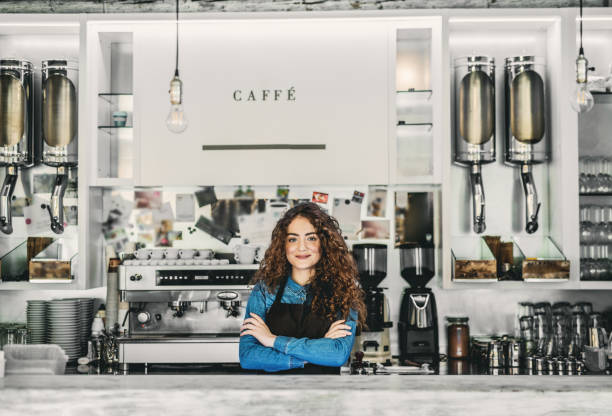 porträt von professionellen junge frau barista hinter einer theke in einem café. - kaffee shop stock-fotos und bilder