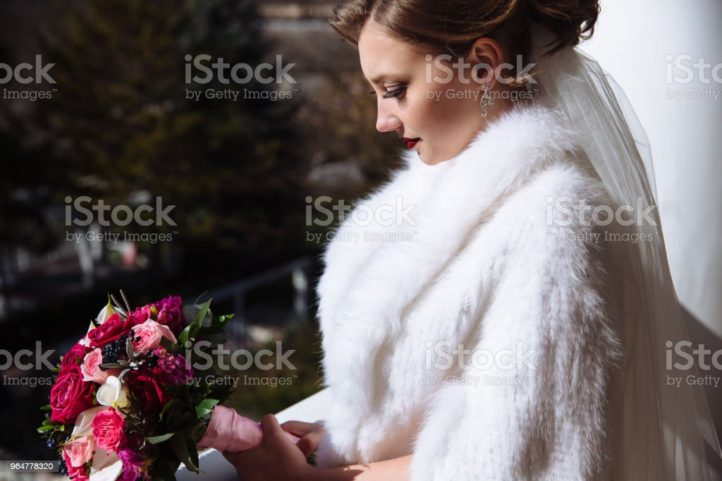Portrait of a profile of a girl with a bouquet of roses. A young woman in a white woolen cape with curls and lipstick on her lips admires flowers royalty-free stock photo