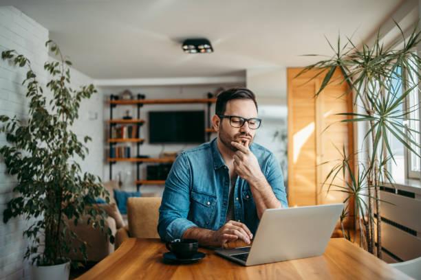 Retrato de un hombre perplejo mirando a la computadora portátil en la casa moderna. - foto de stock