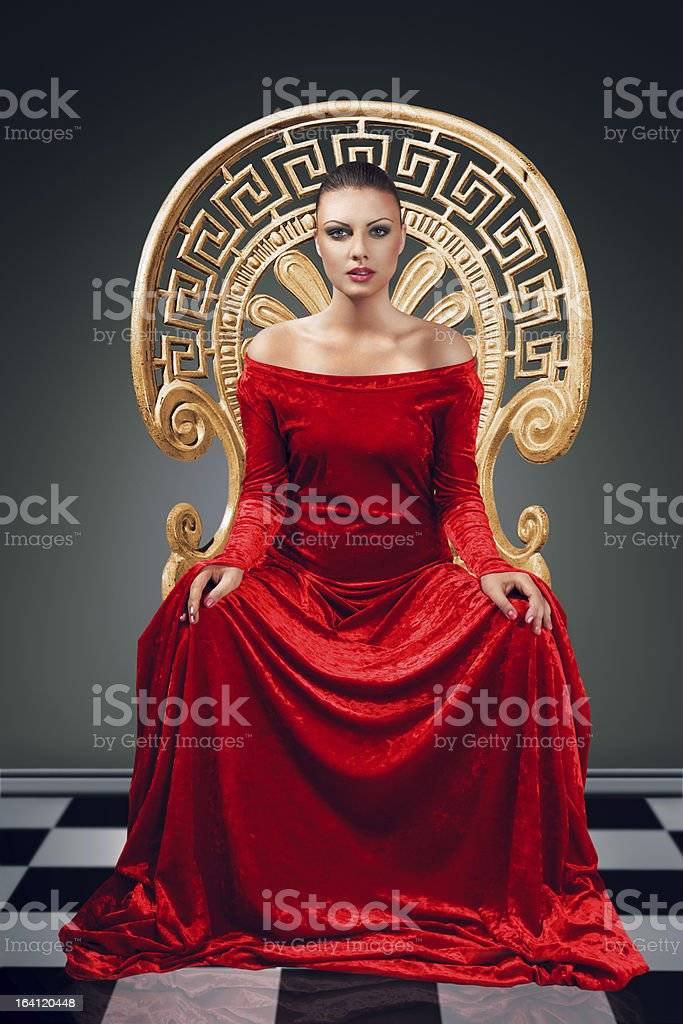 Portrait of a Queen wearing all red in a golden chair stock photo