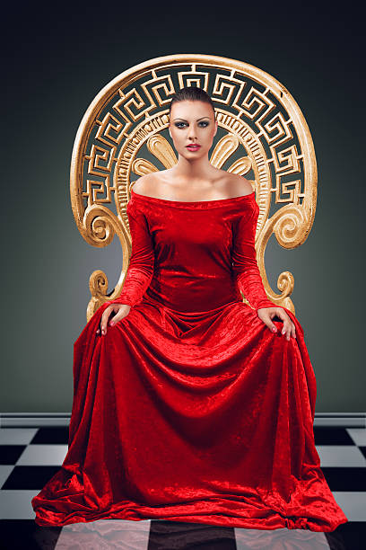 portrait of a queen wearing all red in a golden chair - gothic fashion stock photos and pictures