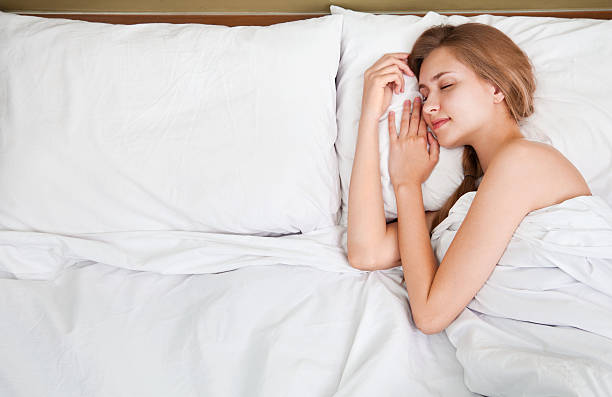 Portrait of a radiant woman sleeping lying on her bed stock photo