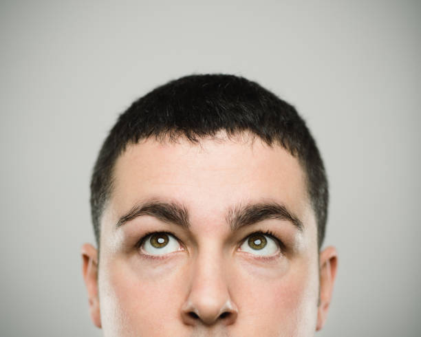 Portrait of a real young caucassian man looking up. Close-up portrait of real young man looking up with blank expression. Serious caucasian male has brown eyes. Real people against white background. Horizontal studio photography from a DSLR camera. Sharp focus on eyes. rolling eyes stock pictures, royalty-free photos & images