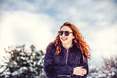 Portrait of a redhead girl with sunglasses at snow