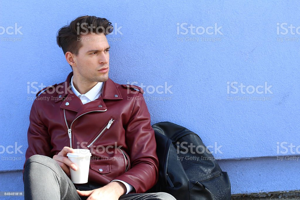 Portrait of a relaxed modern man sitting outdoors stock photo