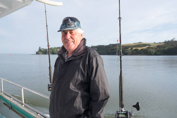 Portrait of a retired senior male tourist on a fishing charter boat at Mangonui, Far North District, Northland, New Zealand, NZ stock photo