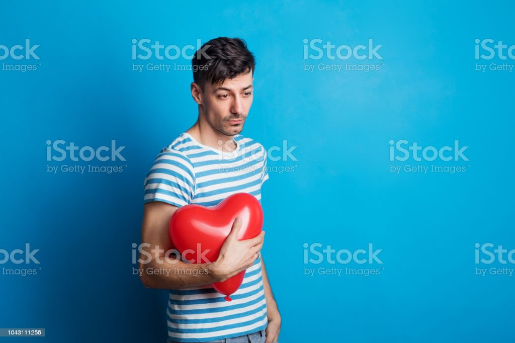 Portrait of a young sad man in a studio on a blue background, holding...