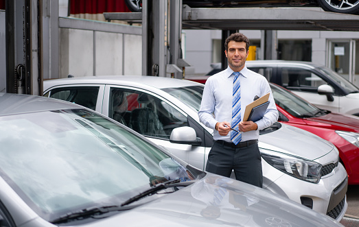 Portrait of a Latin American salesman working at the dealership showing cars outdoors - sales occupation concepts