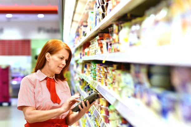 portrait of a saleswoman in the supermarket - supermarket worker imagens e fotografias de stock