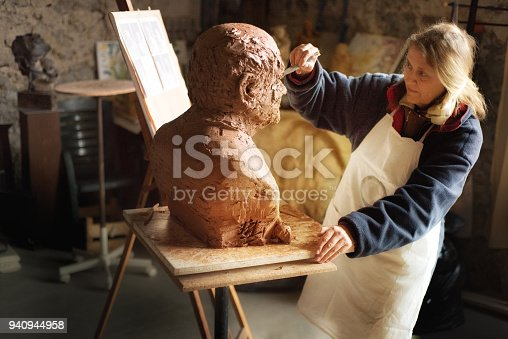 Natural portrait of an artist at work. She is a sculptor who lives and works in la Drome, Provence, France. She is working on a clay bust, with clay figurines and her paintings in the background. Sunlight pours in through the window and she is lost in her work, loving the creative act and her creation.