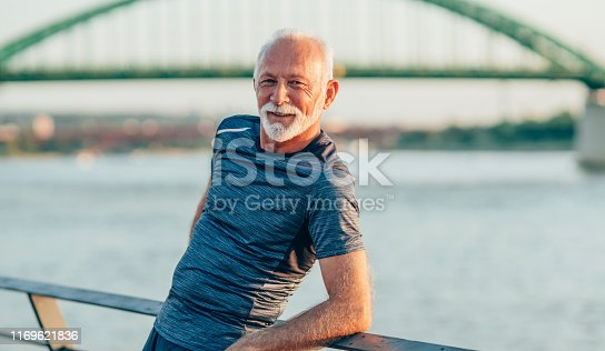 Portrait of a senior athlete leaning on a railing and relaxing after work out.