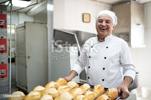 istock Portrait of a senior baker holding a tray full of bread 1268503080