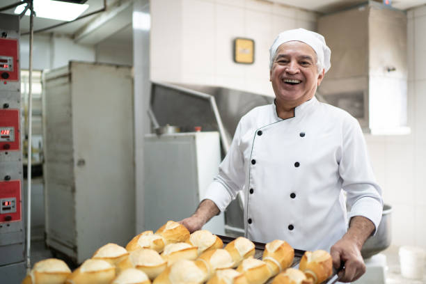 Portrait of a senior baker holding a tray full of bread stock photo