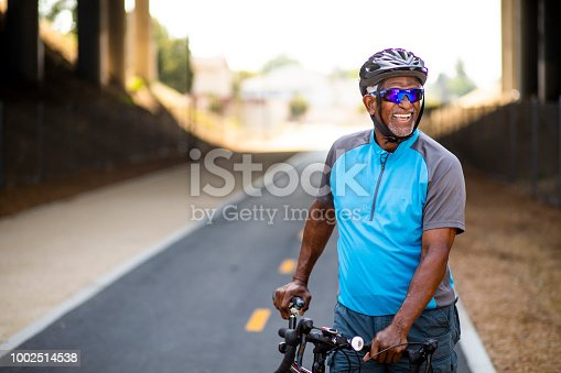 Portrait of a senior black man with his bicycle.