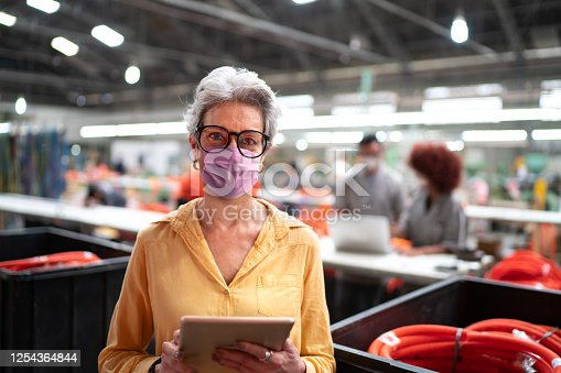 Portrait of a senior businesswoman with face mask using digital tablet and working in a factory