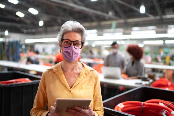 portrait of a senior businesswoman with face mask using digital tablet and working in a industry - senior business woman tablet imagens e fotografias de stock