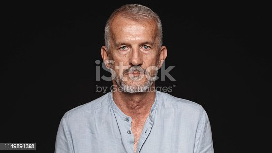 Close up of an old man looking at camera. Portrait of a senior man against black background.