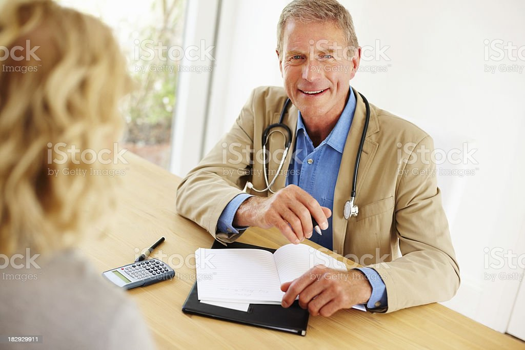 Portrait of a senior doctor with patient in clinic royalty-free stock photo