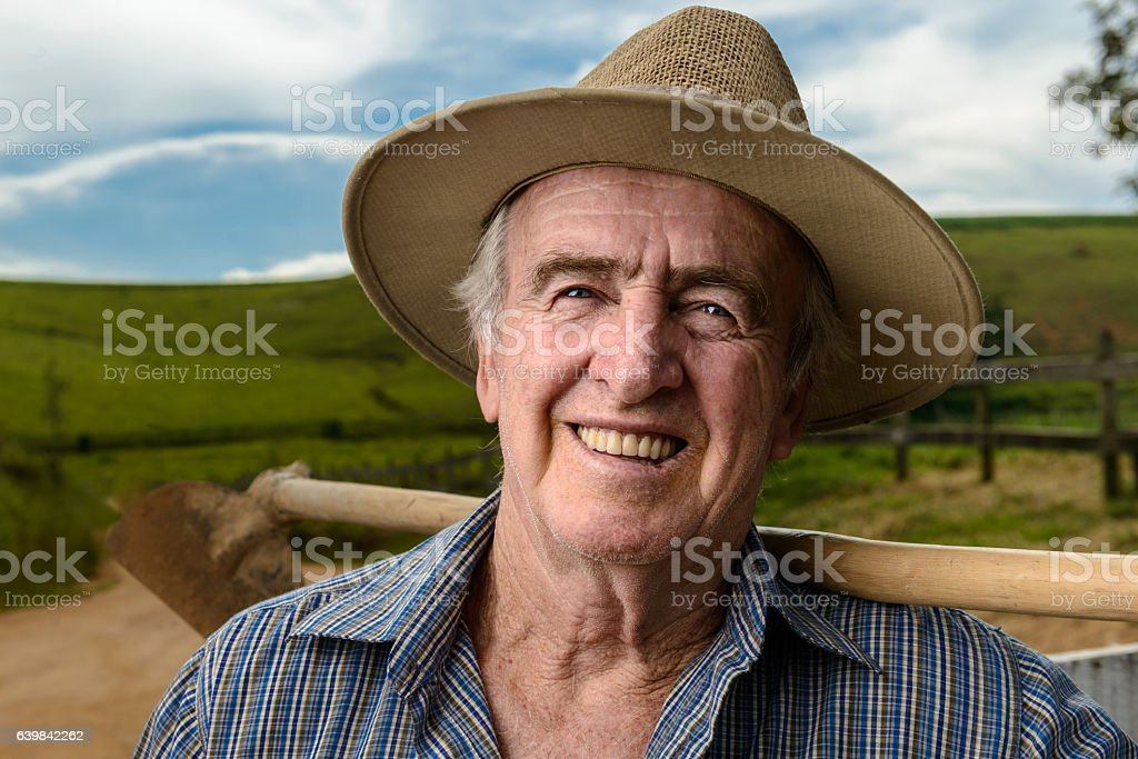 Portrait of a senior farmer holding a hoe, Brazil stock photo