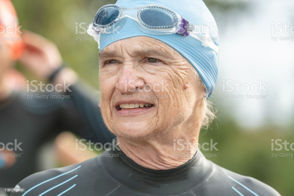 A senior female triathlete looks ahead with an intense and confident...