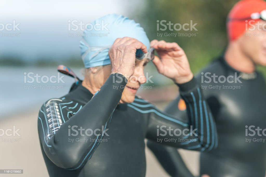 A senior female triathlete adjusts her swimcap. She is in a wetsuit...