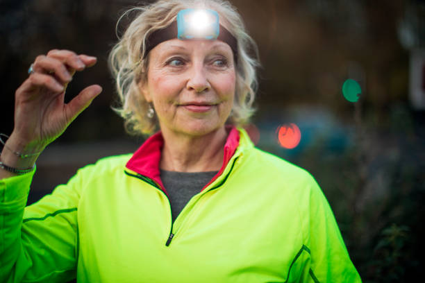 Portrait of a Senior Female Urban Runner A portrait of a mature female urban runner wearing a head torch reflective clothing stock pictures, royalty-free photos & images