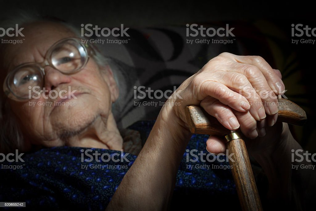 Portrait of a senior lady resting on the walking stick stock photo